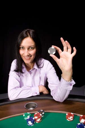 Pretty caucasian girl holds casino chip in hand over black Stock Photo