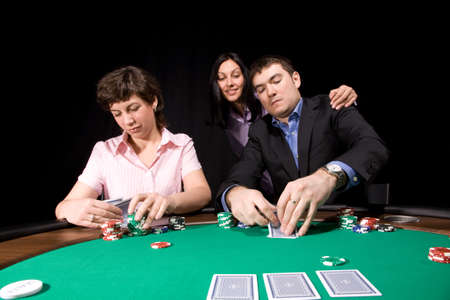 Group of young caucasian adults playing poker on green casino felt