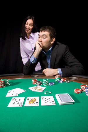 Couple in the casino playing poker on green felt Editorial