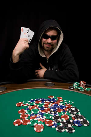 poker table: Man shows two aces and win hand in poker casino with chips on green felt
