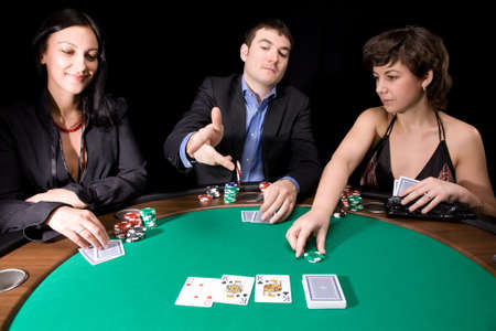 card player: Company of friends having fun with the casino poker table