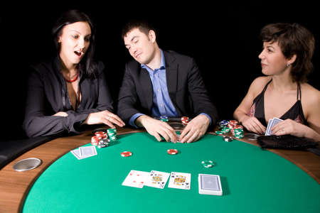 Friends playing poker in the casino at night Editorial