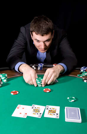 Stylish man in black suit making bet in the casino