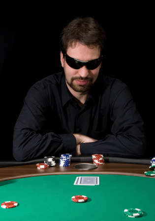 Man in black shirt plaing poker in the casino  Editorial