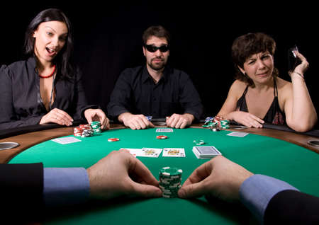 Company of friends having fun in the casino poker table