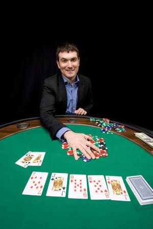 Smiling caucasian man win chips in casino poker