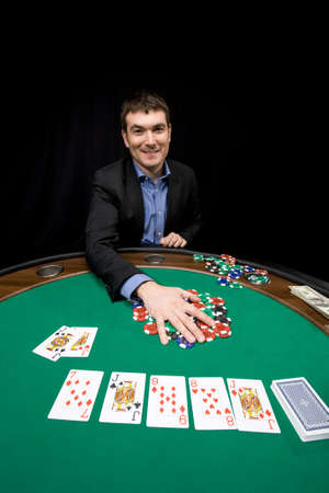 Smiling caucasian man win chips in casino poker