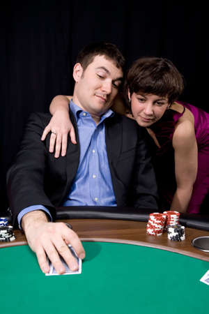 Couple in the casino playing poker on green felt Stock Photo