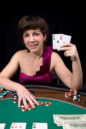 Pretty caucasian girl shows two aces in casino poker Stock Photo