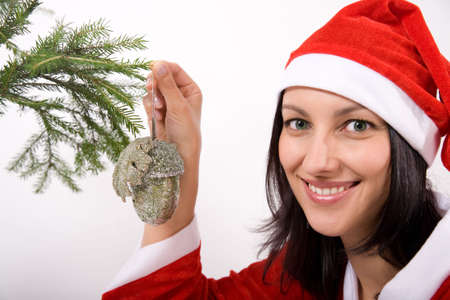 Santa Claus girl hanging toy on christmas tree Stock Photo