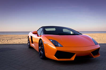sleek: Sleek looking fast sports car background near sand Editorial