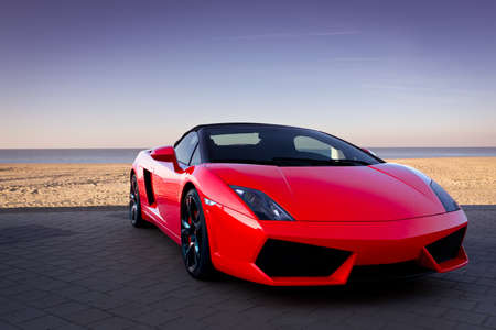 costly: Expensive red sports car at beautiful sunset Editorial