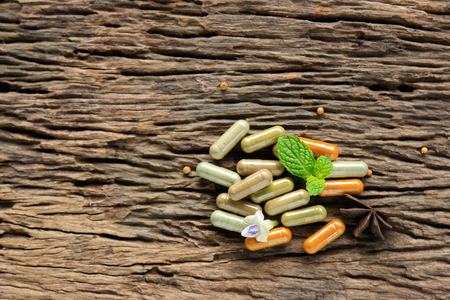 Herbal medicine in capsules powder herb on wooden spoon with mint leaf on rustic wooden table for healthy eating, dieting food for good happy life living Stock Photo