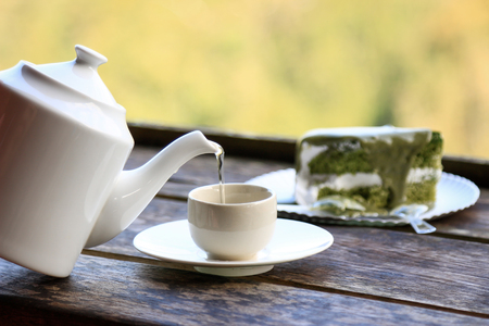 Pouring hot green tea on cup for healthy drinking
