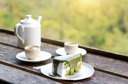 Green tea drinking with cake on wooden table
