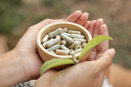 Hand holding herbal medicine for healthy eating