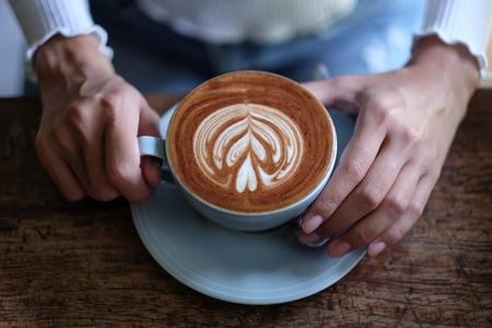 girl holding latte coffee in cafe Фото со стока