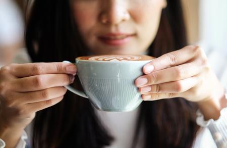 girl holding latte coffee in cafe 版權商用圖片