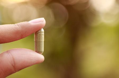 Finger holding herbal medicine with natural background 版權商用圖片