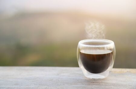 hot coffee glass with nature view in morning time