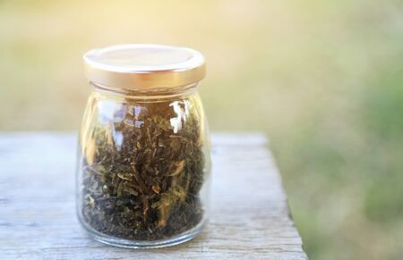 Dry tea leaf in bottle on table