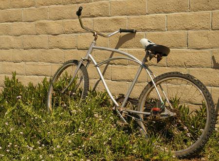 beach cruiser: Bike parked against a wall. Stock Photo