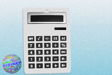 calculator closeup with business words globe in blue background