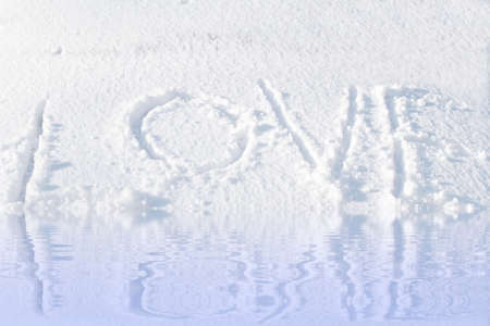 reflection in water: love word on snow background with  water reflection