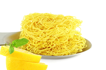 sev: sev  noodles or vermicelli indian food snack with lemon and mint in pure white background