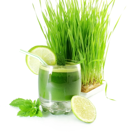 jugos: jugo de pasto de trigo germinado fresco con hierba de trigo en el fondo blanco Foto de archivo