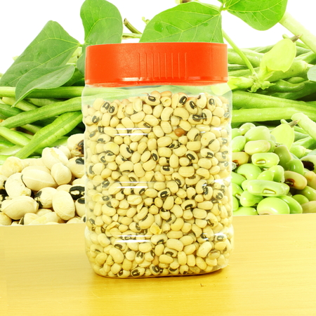 cow pea: Black eye peas beans in jar with fresh beans plant in white background Stock Photo