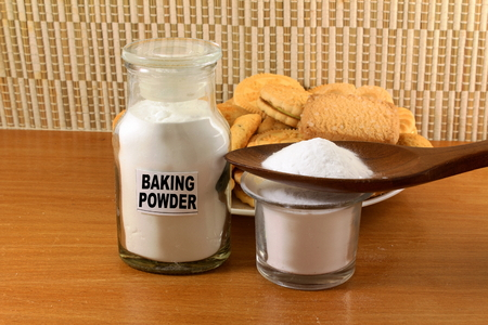 sodium hydrogen carbonate: baking powder in a glass jar and wooden spoon with cookie Stock Photo