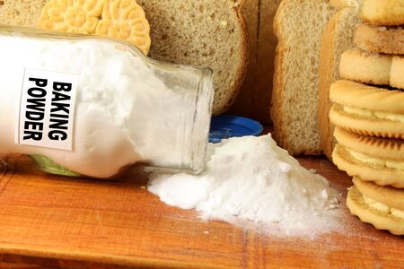 baking powder in a glass jar with cookie and bread