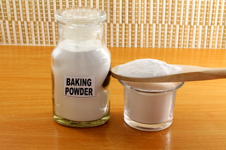 sodium hydrogen carbonate: baking powder in a glass jar and wooden spoon Stock Photo
