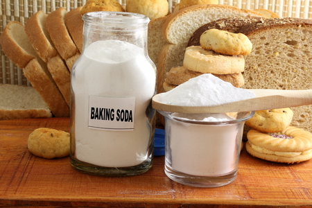 sodium hydrogen carbonate: baking soda in a glass jar and wooden spoon with cookie and bread