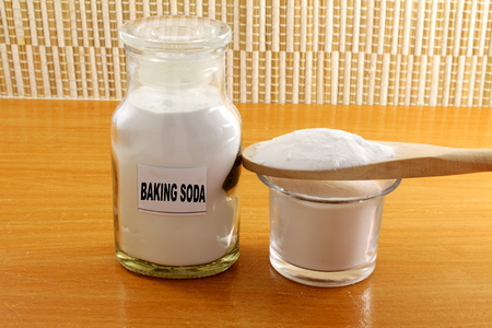 sodium hydrogen carbonate: baking soda in a glass jar and wooden spoon ead