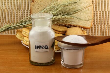 stomach acid: baking soda in a glass jar and wooden spoon with cookie and bread