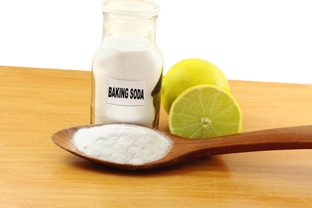 sodium hydrogen carbonate: baking soda in glass bottle and wooden spoon with lemon fruit