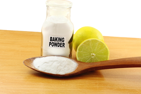 antacid: baking  powder in glass bottle and wooden spoon with lemon fruit Stock Photo