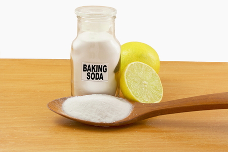 sodium hydrogen carbonate: baking soda  in glass bottle and wooden spoon with lemon fruit Stock Photo