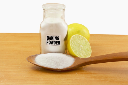 sodium hydrogen carbonate: baking powder in glass bottle and wooden spoon with lemon fruit Stock Photo