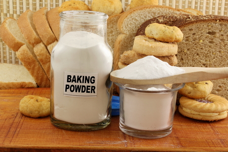 neutralizer: baking powder in a glass jar and wooden spoon with cookie and bread Stock Photo