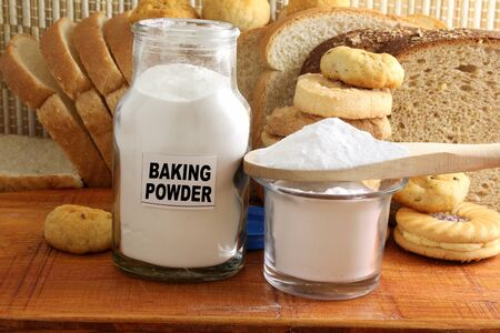 sodium hydrogen carbonate: baking powder in a glass jar and wooden spoon with cookie and bread Stock Photo