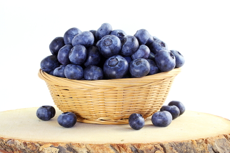 blueberries in bamboo basket on white background
