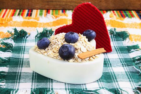 oatmeal bowl: Dry rolled oatmeal flakes  in heart shape bowl with blueberry cinnamon and heart