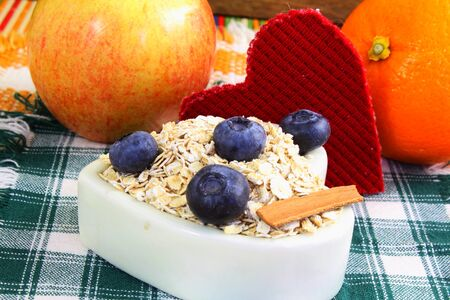 oatmeal bowl: Dry rolled oatmeal flakes  in heart shape bowl with blueberry cinnamon apple orange and heart Stock Photo
