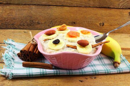 frutas secas: gachas de avena en un recipiente relleno con frutos secos canela plátano