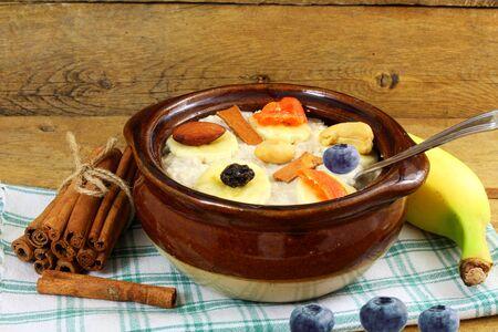 frutas secas: gachas de avena en un recipiente relleno con ar�ndanos canela pl�tano frutos secos