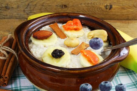 frutas secas: Oatmeal porridge in bowl topping with banana cinnamon blueberries dry fruits