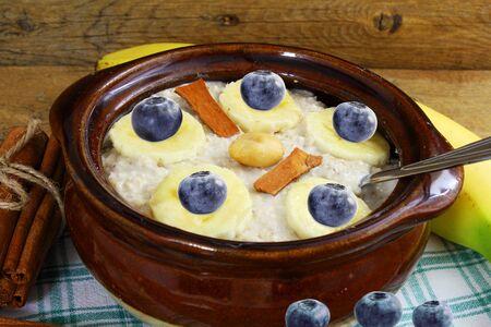 frutas secas: gachas de avena en un recipiente relleno con arándanos canela plátano frutos secos